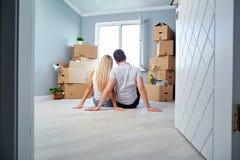 Giovani coppie sul pavimento in una nuova casa immagine stock libera da diritti