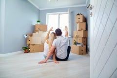 Giovani coppie sul pavimento in una nuova casa immagine stock