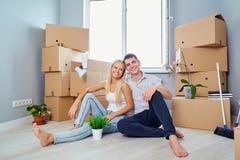 Giovani coppie sul pavimento in una nuova casa housewarming immagini stock