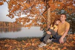 Giovani coppie sulla costa Sunny Autumn Day del lago immagine stock