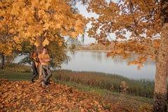 Giovani coppie sulla costa Sunny Autumn Day del lago fotografie stock