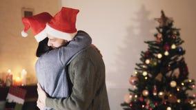 Giovani coppie sveglie in cappelli di Santa che ballano e che abbracciano nella stanza davanti all'albero di Natale Nuovo anno e  video d archivio