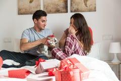 Giovani coppie sveglie che danno un coniglietto come regalo fotografia stock