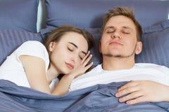 Giovani coppie sveglie che dormono insieme a letto fotografie stock libere da diritti