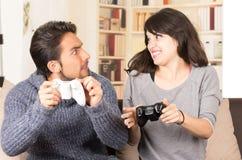 Giovani coppie sveglie che giocano i video giochi Fotografia Stock
