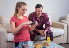 Giovani coppie sveglie che mangiano prima colazione, fotografie al telefono cellulare Fotografia Stock