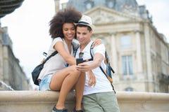 Giovani coppie turistiche che prendono selfie in vacanza in Europa immagini stock libere da diritti