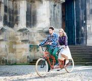 Giovani coppie turistiche, uomo bello e bicicletta in tandem di guida abbastanza bionda della donna lungo la via della citt? fotografia stock libera da diritti