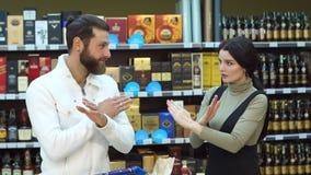 Giovani coppie in un negozio di vino, mostrano che un segno della mano è proibito arresto stock footage