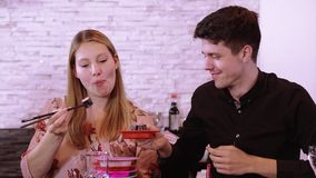 Giovani coppie in un sushi reataurant - mangiare i sushi appena fatti dal buffet stock footage
