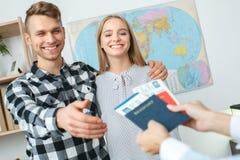 Giovani coppie in una comunicazione dell'agenzia di giro con un concetto di viaggio dell'agente di viaggi che prende i documenti fotografia stock