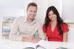 Giovani coppie in una riunione - assicurazione o banca per gli investimenti Immagini Stock