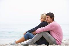 Giovani coppie in vacanza che si siede sulla spiaggia di inverno Fotografia Stock