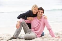 Giovani coppie in vacanza che si siede sulla spiaggia di inverno Fotografia Stock Libera da Diritti