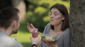 Giovani coppie vegetariane che mangiano insalata e che bevono seduta del frullato al parco video d archivio