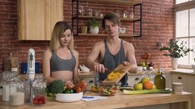 Giovani coppie in vestiti di sport che stanno dietro il tavolo da cucina che prepara sull'insalata fresca del lunc con le verdure archivi video