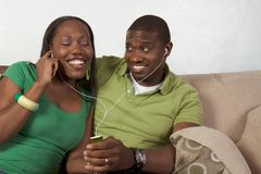 giovani d'ascolto felici etnici di musica delle coppie nere Fotografie Stock