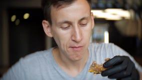 Giovani dell'uomo in guanti neri che mangia un hamburger in un caffè video d archivio