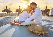 Giovani delle coppie nell'alba di vacanza della spiaggia Immagine Stock