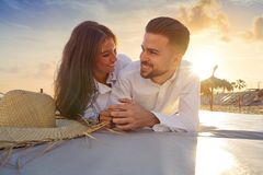 Giovani delle coppie sul tramonto del salotto della spiaggia Immagini Stock Libere da Diritti
