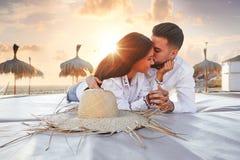Giovani delle coppie sul tramonto del salotto della spiaggia Fotografia Stock