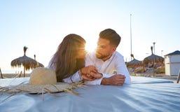 Giovani delle coppie sul tramonto del salotto della spiaggia Immagine Stock