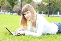 giovani di funzionamento della donna della sosta del computer portatile della città Fotografia Stock Libera da Diritti