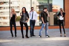 Giovani di modo che rivolgono ai telefoni cellulari Fotografia Stock