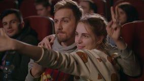 Giovani divertendosi al cinema Coppie di amore che fanno la foto del selfie in cinema stock footage