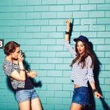 Giovani divertendosi davanti al muro di mattoni blu-chiaro Fotografia Stock