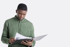 Giovani documenti afroamericani della lettura dell'uomo sopra fondo grigio Immagini Stock