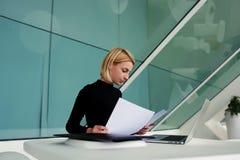 Giovani documenti cartacei intelligenti femminili della lettura del contabile durante il lavoro sul computer portatile Fotografia Stock Libera da Diritti