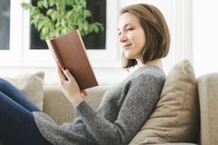 giovani domestici della donna della lettura del libro Immagini Stock Libere da Diritti