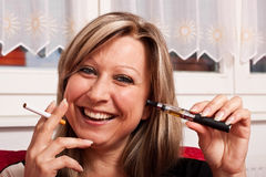 Giovani donna con una sigaretta normale ed elettrico Fotografia Stock
