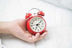 Giovani donna e sveglia addormentate Immagini Stock