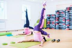 Giovani donne adatte che allungano corpo nello studio di forma fisica Fotografie Stock Libere da Diritti