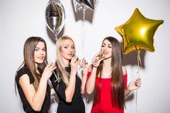 Giovani donne allegre che bevono champagne, parlanti e ridenti con i palloni sul partito fotografia stock