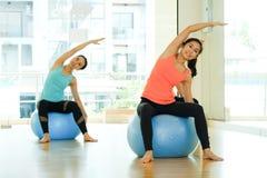 Giovani donne asiatiche che praticano la palla di yoga, allungamento di forma fisica flessibile Fotografie Stock Libere da Diritti