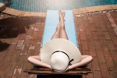 Giovani donne asiatiche che si rilassano il poolside di sonno alla cacca di lusso di nuoto Fotografia Stock