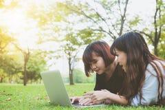 Giovani donne asiatiche che si trovano sull'erba e che usando computer portatile e battitura a macchina Mani delle ragazze sulla  Immagine Stock Libera da Diritti