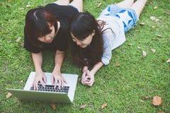 Giovani donne asiatiche che si trovano sull'erba e che usando computer portatile e battitura a macchina Mani delle ragazze sulla  Fotografie Stock