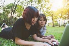 Giovani donne asiatiche che si trovano sull'erba e che usando computer portatile e battitura a macchina Mani delle ragazze sulla  Fotografia Stock Libera da Diritti