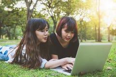 Giovani donne asiatiche dei pantaloni a vita bassa felici che lavorano al computer portatile in parco Studiando nell'erba Fotografie Stock