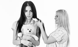 Giovani donne attraenti bionde delle ragazze in pigiami uno che fanno l'altra treccia della treccia concetto di ragazza del parti fotografie stock