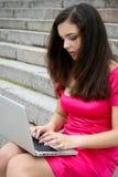 Giovani donne caucasiche dell'allievo con il computer portatile Immagine Stock