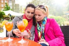 Giovani donne che godono dei cocktail in una barra all'aperto, mentre esaminando telefono cellulare fotografie stock