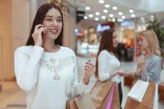 Giovani donne che godono della compera insieme al centro commerciale fotografia stock