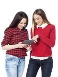 Giovani donne che per mezzo della compressa digitale Fotografie Stock Libere da Diritti