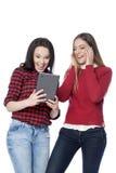 Giovani donne che per mezzo della compressa digitale Fotografia Stock