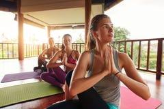 Giovani donne che praticano yoga nella mezza posa spinale di torsione Fotografia Stock